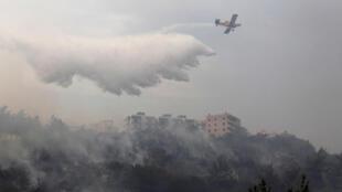 طائرة إطفاء الحرائق تعالج حرائق الغابات في قرية دبية-