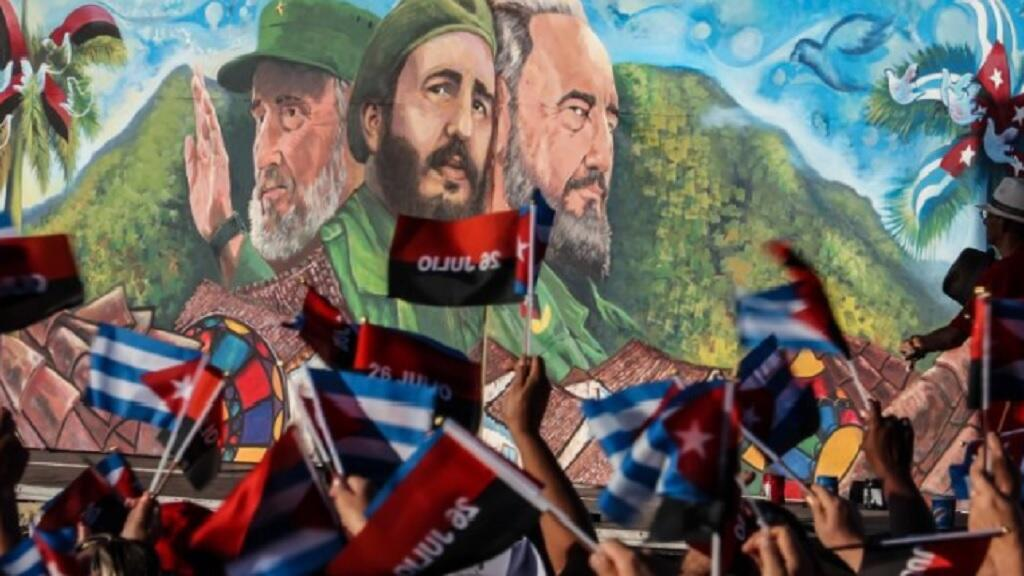 كوبيون يرفعون أعلاما أمام صور كاسترو في تموز/يوليو 2016