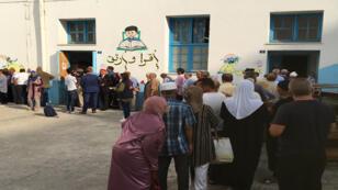 طابور من الناخبين التونسيين أمام مركز اقتراع في تونس العاصمة