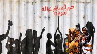 مارة أمام لوحة في أحد شوارع الخرطوم في السودان تحمل شعارات الثورة من حرية وسلام وعدالة ( 10 تموز/ يوليو 2020)