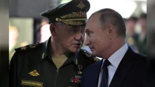 وزير الدفاع الروسي سيرجي شويجو (الى اليسار) يتحدث الى الرئيس فلاديمير بوتين