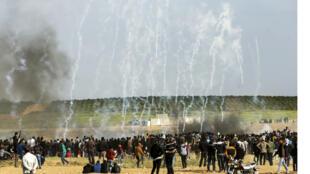 """المتظاهرون الفلسطينيون يركضون وراء غطاء من الغاز المسيل للدموع الذي أطلقته قوات الأمن الإسرائيلية خلال اشتباكات عقب مظاهرة في ذكرى يوم الأرض ، بالقرب من الحدود مع إسرائيل ، شرق مدينة غزة. بعد مرور عام على بدء الاحتجاجات ، أطلق عليها """"مسيرة العودة الكبرى"""" ، واشتباكات على الحدود بين غزة وإسرائيل"""
