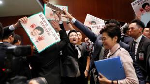 رئيسة السلطة التنفيذية في هونغ كونغ كاري لام اثناء خروجها من البرلمان وسط هتافات المعارضة