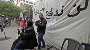 حلاق تبرع مجانا بقص شعر متظاهرة تطالب بالإقتطاع من ودائع الأغنياء في بيروت