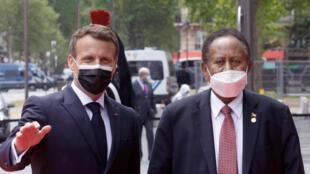 الرئيس الفرنسي إيمانويل ماكرون يرحب برئيس الوزراء السوداني عبد الله حمدوك قبل انعقاد مؤتمر دولي حول السودان، في باريس في 17 مايو 2021.