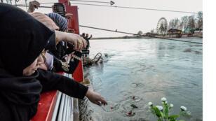نساء راقيات يلقين الزهور في نهر دجلة في ذكرى ضحايا العبارة المنكوبة في مدينة الموصل شمال العراق في 22 مارس 2019 ، في أعقاب الحادث الذي خلف 100 قتيل على الأقل