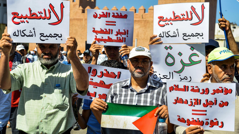 المدافعون يرفعون لافتات تحث على تطبيع العلاقات مع إسرائيل أثناء تعليقهم لافتة تظهر العلم الفلسطيني خلال مظاهرة في العاصمة المغربية الرباط في 23 يونيو 2019 ضد المؤتمر الاقتصادي الذي تقوده الولايات المتحدة في البحرين بهدف معلن هو تحقيق الرخاء الفلسطيني
