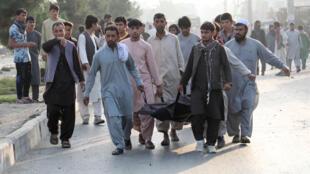 رجال أفغان يحملون جثة مدني في موقع انفجار في كابول