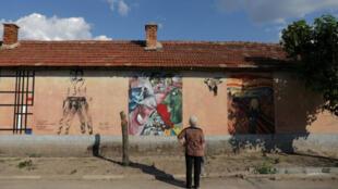 امرأة تشاهد اللوحات الفنية على حائط بقرية بلغارية