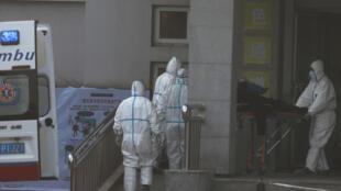 ممرّضون صينيون يحاولون إسعاف مصاب بفيروس جديد بادخاله للمستشفى