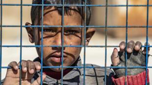 طفل ينتظر المغادرة أثناء إطلاق سراح مجموعة أخرى من العائلات السورية من مخيم الهول الذي يديره الأكراد، حيث يحتجز أقارب مشتبه بهم لمقاتلي تنظيم الدولة الإسلامية، في محافظة الحسكة شمال شرق سوريا، في 20 فبراير2021.
