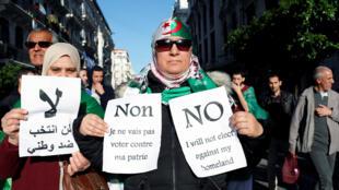المتظاهرون يحملون لافتات أثناء مشاركتهم في احتجاج للمطالبة بإلغاء الانتخابات الرئاسية المقرر إجراؤها الأسبوع المقبل ، في الجزائر العاصمة-