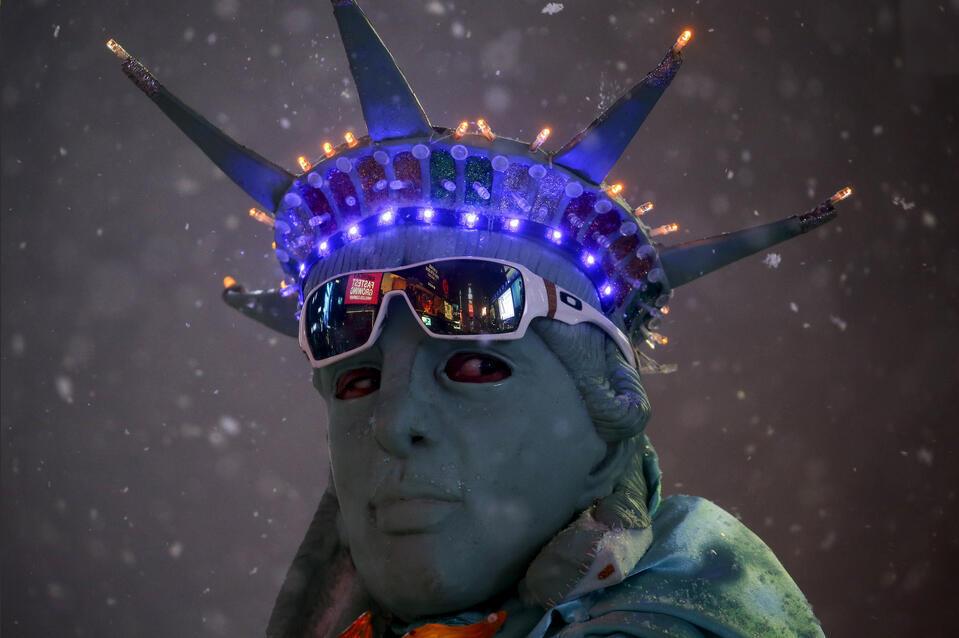 """رجل متنكر بشكل تمثال الحرية في ساحة """"التايمز سكوير"""" أثناء العاصفة"""
