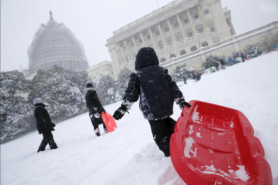 طفل يلهو بقارب فوق الثلج في العاصمة واشنطن