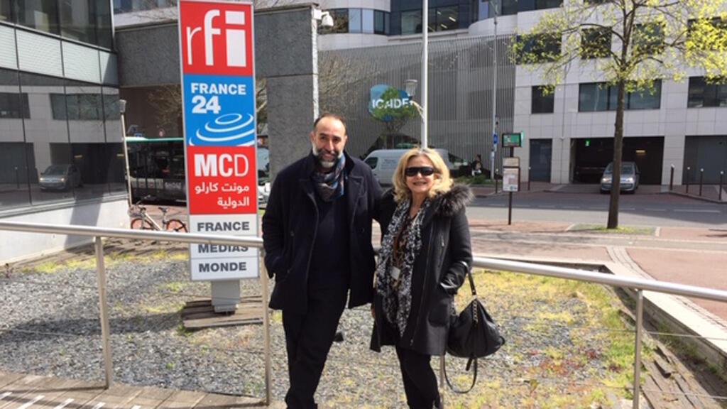 المصمم اللبناني ربيع كيروز رفقة الإعلامية كابي لطيف (أمام مبنى إذاعة مونت كارلو الدولية، باريس)