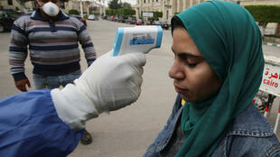 A master's degree student reacts as medical staff member checks her temperature amid concerns over the coronavirus (COVID-19), following the suspension of study for only undergraduate students at Cairo University to prevent it spreading, in Cairo, Egypt March 15, 2020. REUTERS/Shokry Hussien
