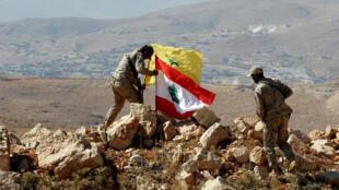 """مقاتل من """"حزب الله"""" يضع علمي لبنان والحزب في بلدة عرسال اللبنانية"""