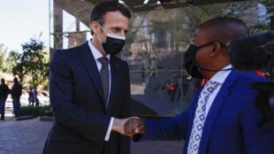 إيمانويل ماكرون يصافح مدير مؤسسة نيلسون مانديلا
