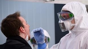أحد العاملين في القطاع الصحي يجري اختبارا للكشف عن فيروس كورونا في مركز صحي استُحدث خصيصا في منطقة درسدن شرق ألمانيا