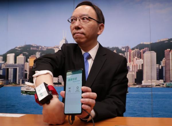 فيكتور لام، كبير مسؤولي المعلومات في حكومة هونغ كونغ يعرض سوار المعصم المتصل لمراقبة  الحجر الإلزامي لمن يشتبه بتعرضهم لفيروس كورونا المستجد .