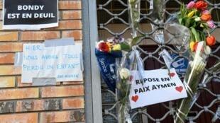 """لافتة تحمل عنوان """" البارحة خسرنا جميعا ولداً """" والتوقيع """"أمٌ""""، موضوعة بالقرب من باقات من الزهور حيث قُتل الشاب أيمن في ربيعه الخامس عشر، في ضاحية بوندي الباريسية ( 26 فبراير 2021)"""