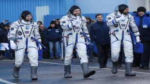 أعضاء الطاقم ديفيد سانت جاك من كندا ، وأوليج كونونينكو من روسيا و آن ماكلين من الولايات المتحدة سيرا على الأقدام بعد ارتداء بدلات الفضاء قبل وقت قصير من انطلاقهم