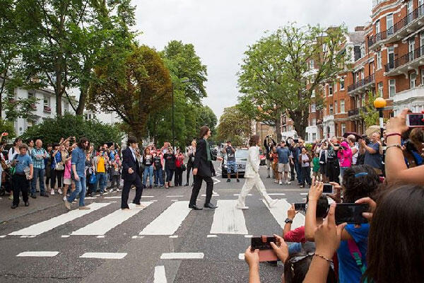"""صورة عن صفحة Abbey Road Studios على الفيس بوك يظهر فيها أربع شبان يقلدون الـ """"بيتلز"""" في الصورة الشهيرة لهم"""