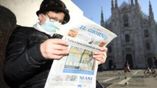 امرأة إيطالية تتطالع الجريدة مرتدية القناع خوفا من فيروس كورونا