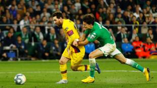 مدافع من فريق ريال إشبيلية يحاول بكل السبل منع ليونيل ميسي من مواصلة التقدم نحو مرمى فريقه