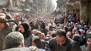 حشود من سكان مخيم اليرموك في دمشق يحاولون الحصول على مساعدات غذائية إثر حصار النظام للمخيم في بدايات عام 2014