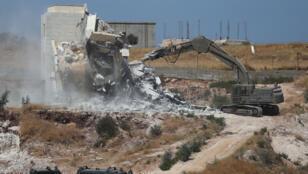 الآليات العسكرية الإسرائيلية تهدم مبنى فلسطينيا في قرية صور باهر تقع على جانبي الجدار الإسرائيلي في القدس الشرقية والضفة الغربية التي تحتلها إسرائيل