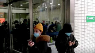 صينيون يضعون أقنعة بأحد مستشفيات ووهان الصينية