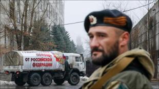 مقاتل انفصالي موال لروسيا أمام شاحنة مساعدات روسية في ماكييفكا التابعة لمنطقة دونيتسك في 12 كانون الأول 2014