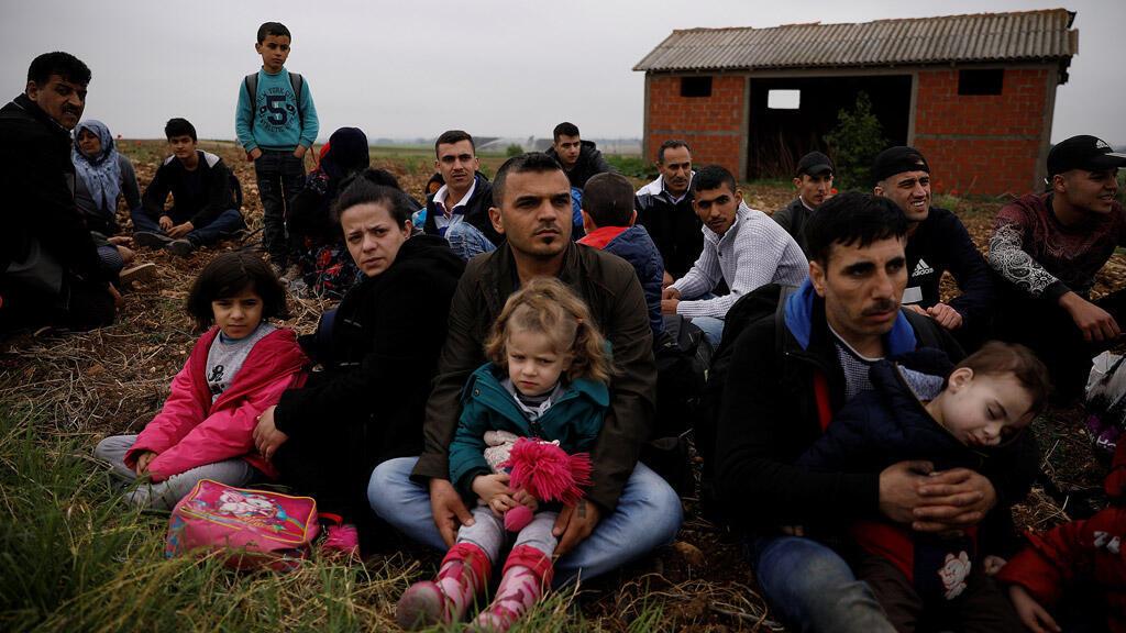 اللاجئون السوريون يجلسون في حقل بين الحدود اليونانية التركية
