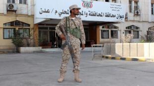 عنصر من قوى الأمن اليمنية يقف حارسا أمام محكمة العدل، عدن