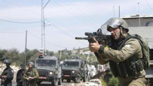 جندي إسرائيلي يوجه سلاحه نحو المتظاهرين الفلسطينيين في اشتباكات بالقرب من مستوطنة بالقرب من نابلس في الضفة الغربية المحتلة.