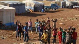 أطفال يتجمعون في مخيم للاجئين من إدلب وحماة على الحدود السورية-التركية (26-08-2018)