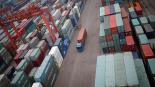 شاحنة تتنقل بين حاويات الشحن في ميناء إنتشون-