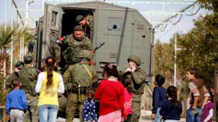أطفال سوريون مع جنود في مخيم الوافدين في دمشق