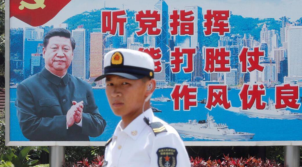 جندي من جيش التحرير الشعبي الصيني يقف أمام خلفية تبرز الرئيس الصيني شي جين بينغ