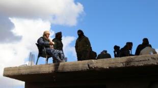 مقاتلون من قوات سوريا الديمقراطية فوق سطح في بلدة الباغوز الفوقاني في ريف دير الزرو في شرق سوريا