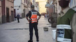 رجال من الشرطة المغربية يقفون لحراسة شارع يوم 8 يونيو 2020 بعد أن تم اكتشاف العديد من حالات Covid-19 في مصنع لتعليب الأسماك في مدينة آسفي الساحلية الجنوبية