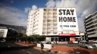 """مدينة كايب تاون في جنوب إفريقيا مقفرة  بسبب أزمة كورونا، مع لائحة عريضة على أحد المباني تقول """"إبقوا في بيوتكم"""""""