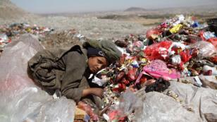 صبي يقوم بجمع أشياء من مكب للنفايات في ضواحي صنعاء