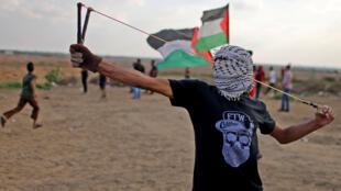 متظاهر فلسطيني يستخدم مقلاعًا خلال مظاهرة مناهضة لإسرائيل عند السياج الحدودي بين إسرائيل وغزة في جنوب قطاع غزة-