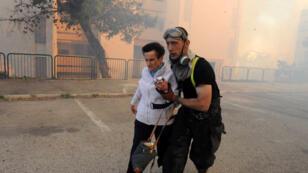 أحد رجال الاسعاف يجلي إمراة مسنة في شمال مدينة حيفا