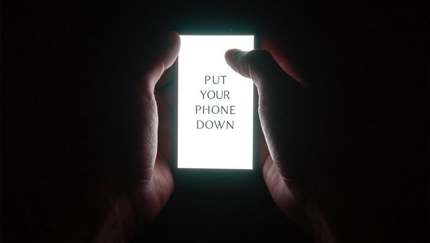 هاتف مكتوب عليه بالانكليزية: ضع الهاتف من يدك