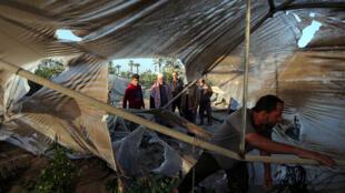 فلسطينيون يتفقدون موقعًا تابعًا لحركة حماس بعد استهدافه من قبل الطائرات الحربية الإسرائيلية في جنوب قطاع غزة-