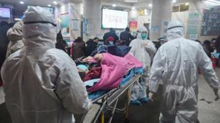 طاقم طبي يرتدي ملابس واقية للحماية من فيروس كورونا مع أحد المرضى في مستشفى ووهان يوم 25 يناير/ كانون الثاني 2020