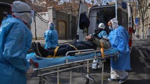 طاقم طبي يحمل مريضا يشتبه بإصابته بفيروس كورونا في ووهان الصينية